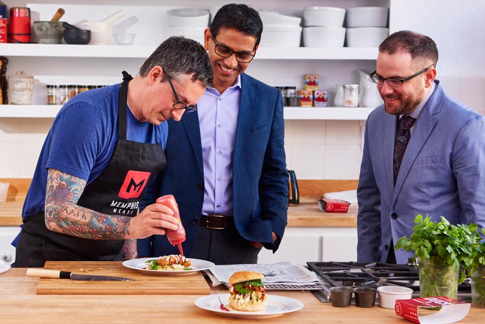Memphis Meat CEO Uma Valeti bestaunt die Herstellung seines Hühnchensandwiches.