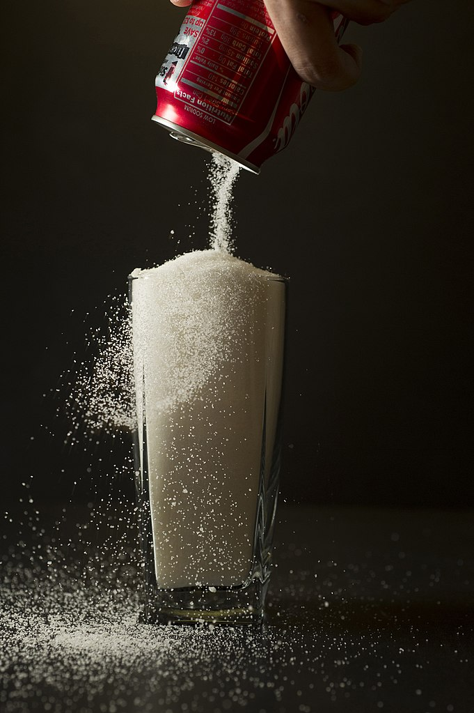 Sugar is poured from a can of coke into a glass.